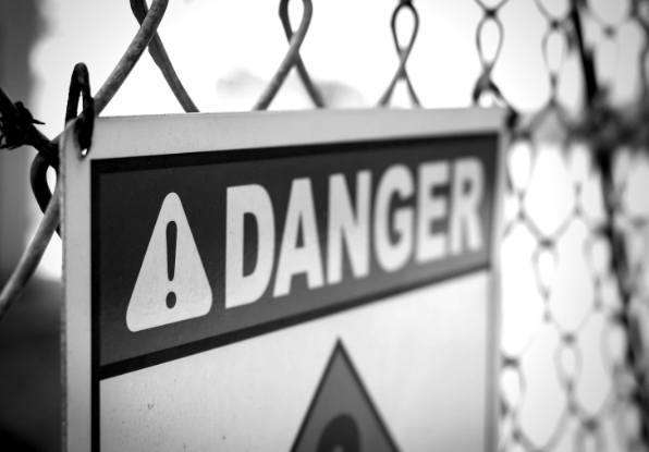 Image of danger - keep out sign on perimeter fence.